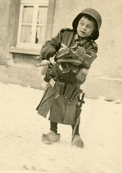 Ein kleiner Moerser Junge in Wehrmachtsuniform mit Waffe und Gasmaske um 1940. (Original: Privatbesitz)
